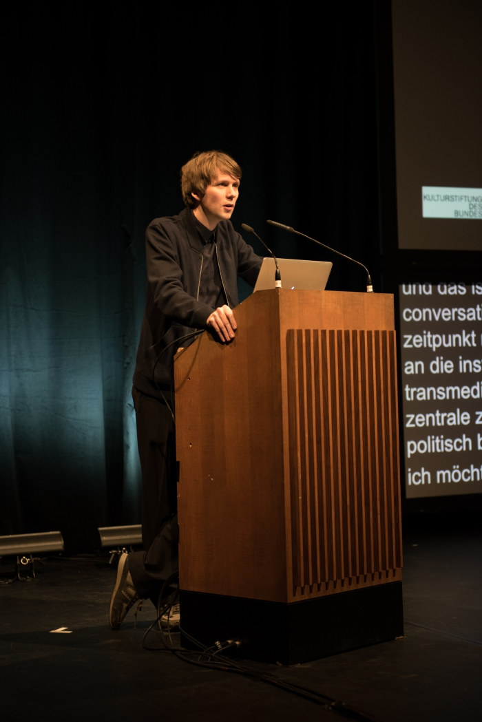 """Picture of Kristoffer Gansing announcing the Keynote Conversation """"Anxious to Act"""""""